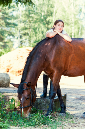 Young teenage cheerful girl equestrian hugging her favorite chestnut horse. Vibrant multicolored summertime outdoors vertical image.