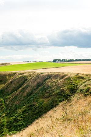 Golden scottish wheat fields and ravines in Dunnottar. Panoramic view from highlands. Scotland. Uk. Aberdeen. Multi-colored summertime outdoors vertical image.