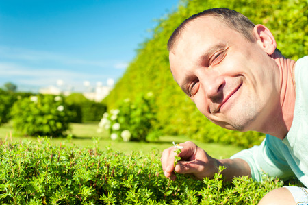 Love the nature-save your planet! Happy man face with small flower in green summer park. Outdoors horizontal image.