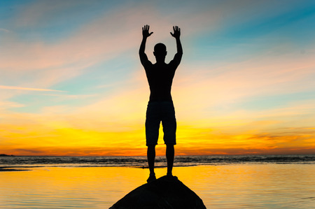 Photo pour Inspired man silhouette standing in rays of sunlight with raised up arms on blue sky background. Multi-colored vibrant summertime outdoors horizontal image. Copy space. - image libre de droit