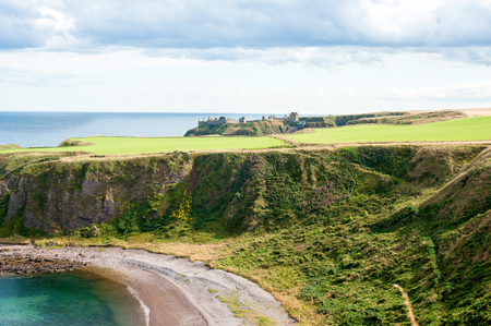 Curves of scottish fields and ravines in Dunnottar. Panoramic view from highlands. Scotland. Uk. Aberdeen. Vibrant colored summertime outdoors horizontal image with dramatic cloudy sky background.