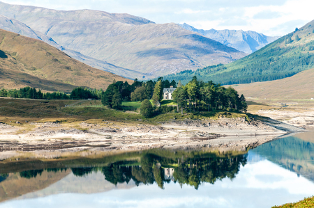 Landscape with beautiful view of small scottish house in wild mountains, lake with reflection and woodland. Loch Cluanie fort William. Scotland. Uk. Vibrant colored summertime outdoors horizontal image
