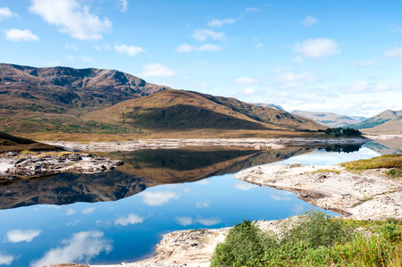 Landscape with beautiful scottish wild mountains and lake with reflection. Panoramic view. Loch Cluanie fort William. Scotland. Uk. Vibrant colored summertime outdoors horizontal image with cloudy sky background.