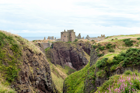 Ruins of ancient Dunnottar castle in green scottish hills. Panoramic view from highlands. Scotland. United Kingdom. Multi-colored summertime outdoors horizontal image.
