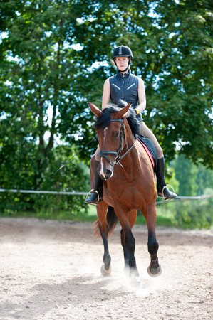 Photo pour Training process. Young teenage girl riding bay horse on arena at equestrian school. Colored outdoors vertical summertime image. - image libre de droit
