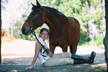 Photo pour Young teenage cheerful girl equestrian hugging her favorite chestnut horse. Vibrant multicolored summertime outdoors horizontal image with filter - image libre de droit
