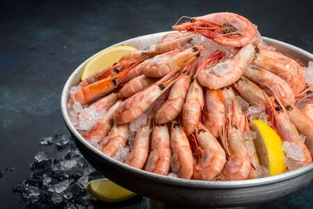 A lot of prawns with lemon in an iron dish. Close-up shotの素材 [FY310142684533]