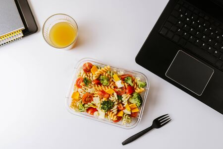 Healthy food in lunch box, on working table with laptop .Ensalada de pasta brocoli con queso y verduras. eating at workplace. Home food for office concept