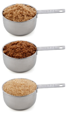 Different sugars - light brown soft or muscovado, dark brown soft or muscovado and demerera - in cup measures, isolated on a white background