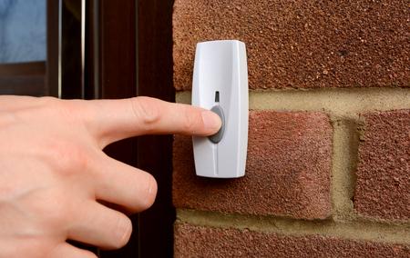 Foto für Close-up of woman pressing the button of a doorbell on a brick wall - Lizenzfreies Bild