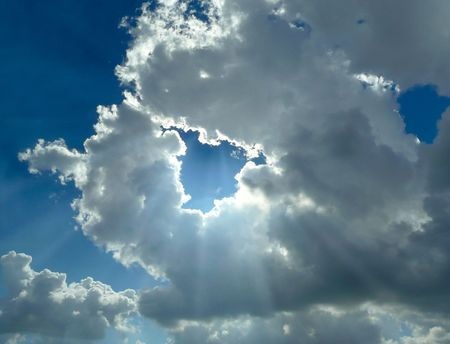 sun rays and silver lining of white clouds on blue sky