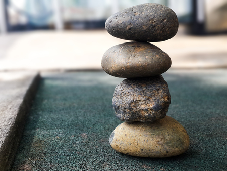 Four stones stacking up in balance on greenish floor.