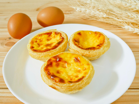 Fresh baked egg tarts or custard tarts (pastel de nata) on a white plate