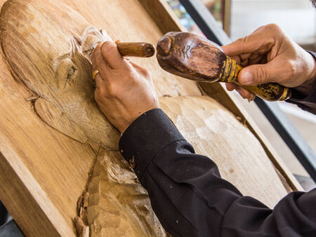 hands of the craftsman carve a bas-relief