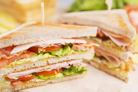 A club sandwich on a rustic table in bright light.