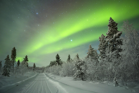 Spectacular aurora borealis northern lights on a track through winter landscape in Finnish Lapland.