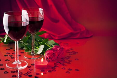 A romantic still life with two glasses of red wine, a heart shaped candle and two roses, with a soft satin background.