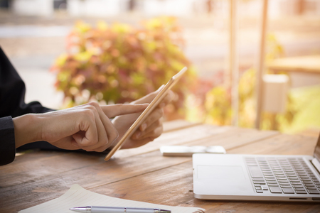 Foto de Businessman using tablet working with  laptop on wood table. - Imagen libre de derechos