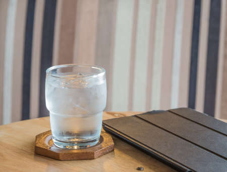 Drinking water in the glass, tablet placed on a wooden table.