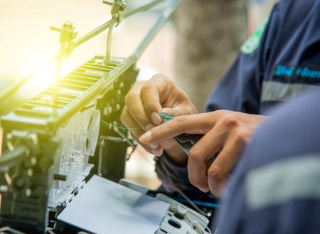 Photo pour Technicians are install cabinet on fiber optic cable.Blur images with back lighting. - image libre de droit