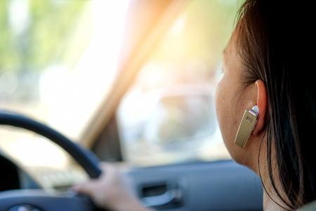 Photo pour Women using hands-free phone while driving a car. - image libre de droit