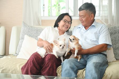 Photo pour Elderly are sitting happily resting on the sofa with the dogs. - image libre de droit