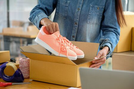 Photo pour Online sellers are packing shoes in boxes to deliver to customers. - image libre de droit