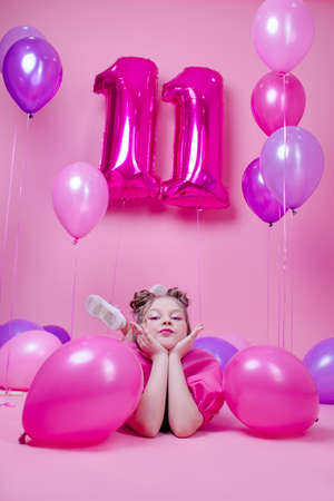 Photo pour sweet brunette girl with pink make up and in pink leather dress. near colorful balloons in shape of number eleven. on pink background.concept of joy, party, birthday celebration - image libre de droit