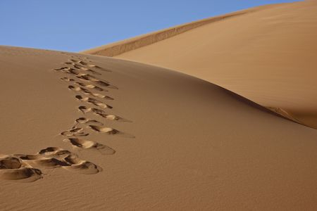 footprints on desert sand dune with blue sky