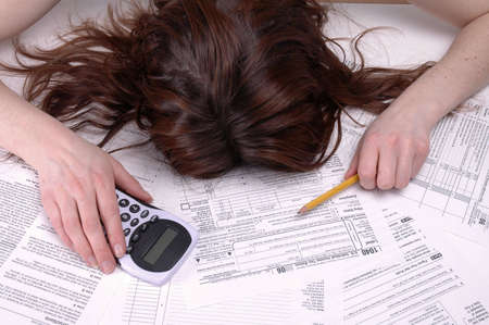A woman slumped over in despair on a pile of tax forms.