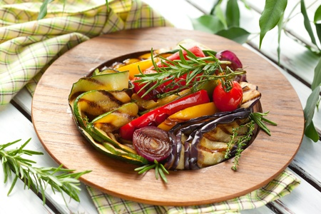 Grilled vegetables with rosemary and thyme on the wooden plate