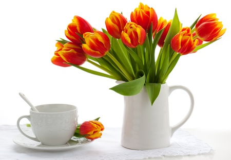 red tulips in a jug and cup of tea on white