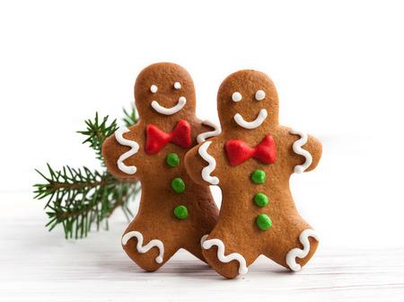 Smiling gingerbread men on white wooden background