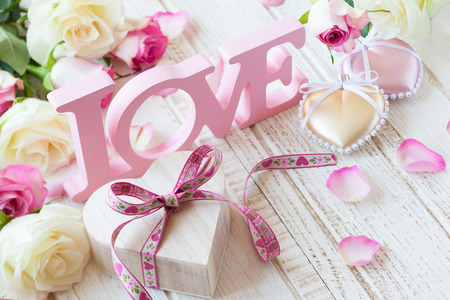 Valentine's day concept with gift box, letters love and flowers on old vintage wooden background