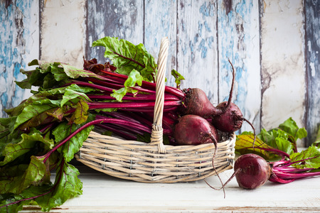 Fresh organic beetroot with green leaves in a basket