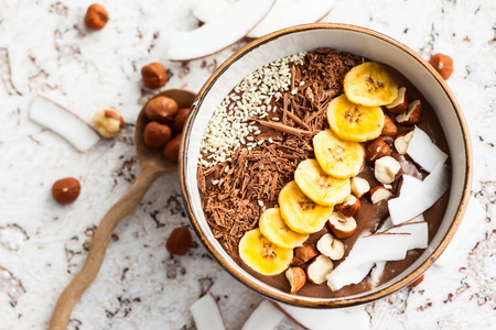 Chocolate hazelnut smoothie bowl topped with sliced banana shredded coconut chopped chocolate nuts and sesame seeds.