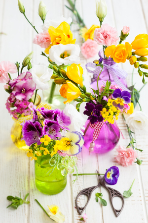 Photo pour Beautiful fresh flowers in glass bottles on the wooden table - image libre de droit