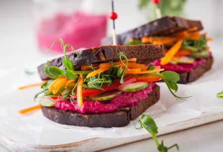 Photo pour gluten free vegan sandwiches with beet hummus, raw vegetables and sprouts. soft focus - image libre de droit