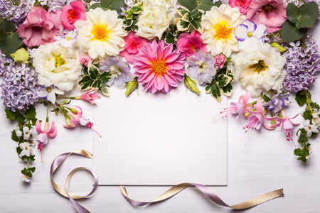 Photo pour Festive flower composition with greeting card on the white wooden background. Overhead view - image libre de droit