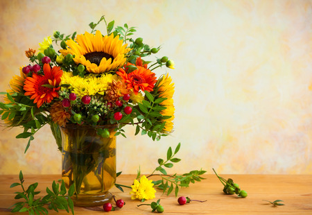 autumnal flowers and berries in a vase