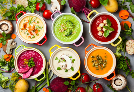 Foto de Variety of colorful vegetables cream soups and ingredients for soup. Top view. Concept of healthy eating or vegetarian food. - Imagen libre de derechos