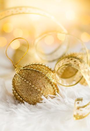 Photo pour Gold Christmas baubles on white fur with gold sparkling background. Festive winter concept. - image libre de droit
