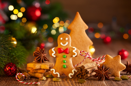 Foto de Christmas homemade gingerbread cookies and spices on the wooden background - Imagen libre de derechos