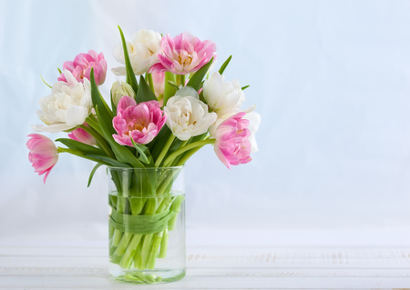 Foto de Fresh bouquet of spring tulips  on white wooden table. - Imagen libre de derechos
