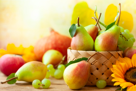 Autumn still life with seasonal fruits,flowers and vegetables on wooden background.