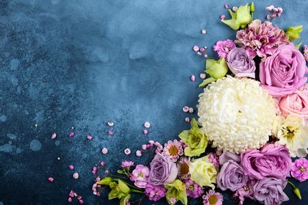 Foto de Beautiful  flowers on vintage blue background. Festive floral concept with clean space for text. Top view. - Imagen libre de derechos