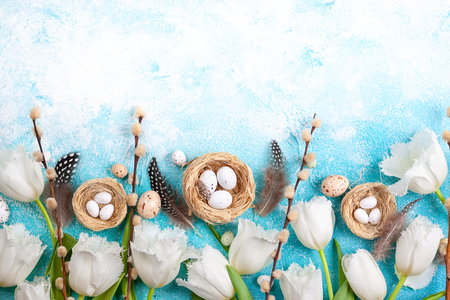 Foto de Easter composition with Easter eggs in nest,pussy willow branches and white tulips on the blue background. Bunch of spring flowers and Easter decor. Top view with copy space. - Imagen libre de derechos