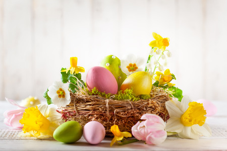 Foto de Easter composition with colorful Easter eggs in nest, spring flowers - Imagen libre de derechos