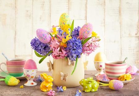 Foto de Easter breakfast table with tea, eggs in egg cups, spring flowers in vase and Easter decor. - Imagen libre de derechos
