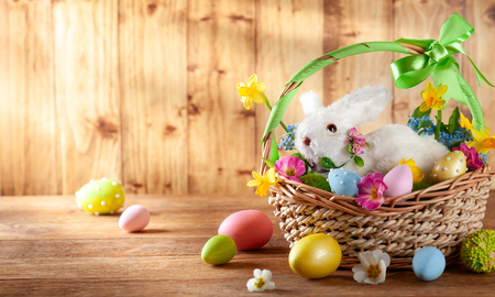 Photo for Easter composition with little white bunny in basket,  spring flowers and colorful Easter eggs . Easter Card with copy space. - Royalty Free Image